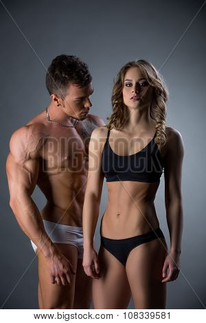 Bodybuilder admires pretty girl with perfect body