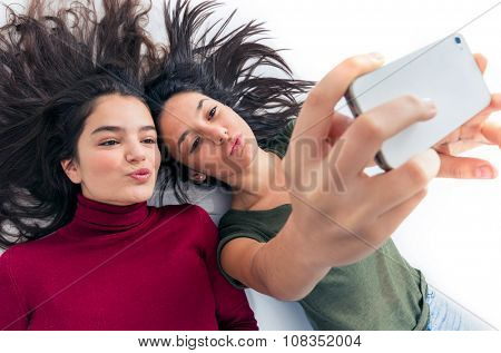 Two joyful teenager girl friends laying on the floor taking a selfie
