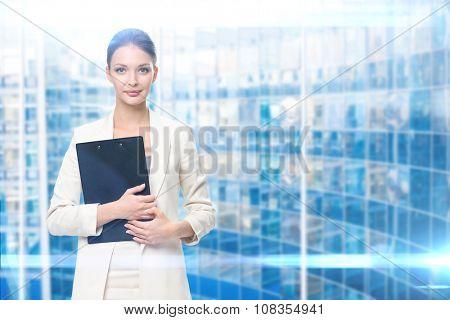 Portrait of businesswoman handing black folder, blue background. Concept of leadership and success