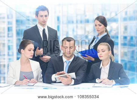 Group of executives discussing while sitting at the table, blue background. Concept of teamwork and cooperation