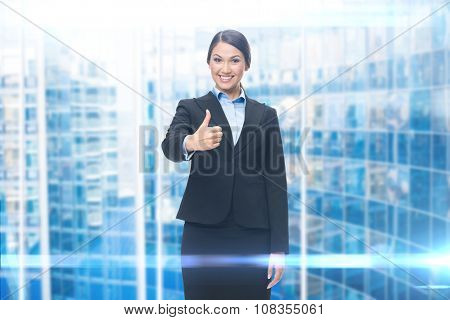 Portrait of businesswoman thumbing up, blue background. Concept of leadership and success