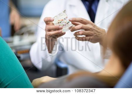 Close up of dentist holding model of teeth with colorful braces
