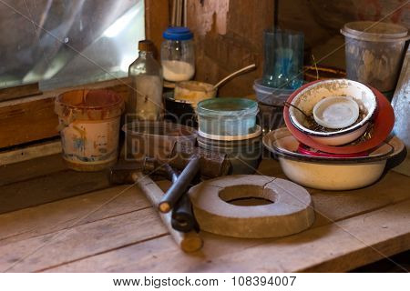 a wooden table in a rustic barn where tools are hammers grindstone, banks and nails