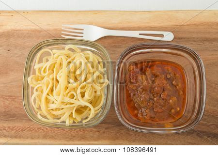 a small portion of linguini pasta and pasta tomato sauce in a glass storage container