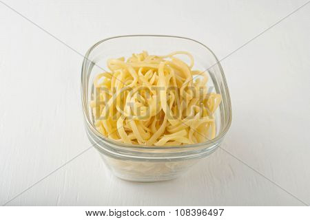 a small portion of linguini pasta in a glass storage container on white background
