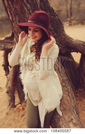 adorable pregnant woman in fashion hat on warm cozy outdoor walk on riverside poster