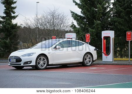 White Tesla Model S Being Charged At Supercharger Station