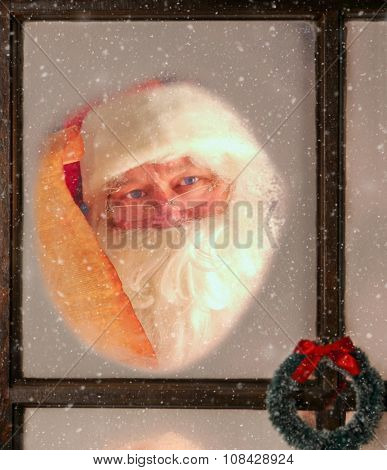 Santa Claus seen through the frosted window of his North Pole Workshop holding his Naughty and Nice List. It is snowing outside.