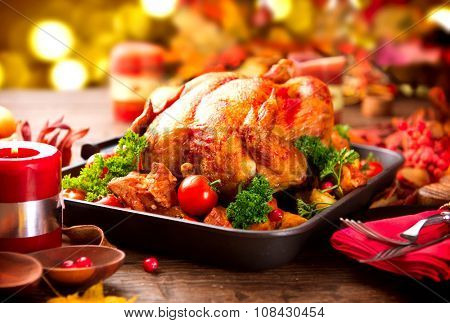 Christmas Dinner. Roasted Turkey on holiday served table, decorated with candles. Roasted chicken, table setting.