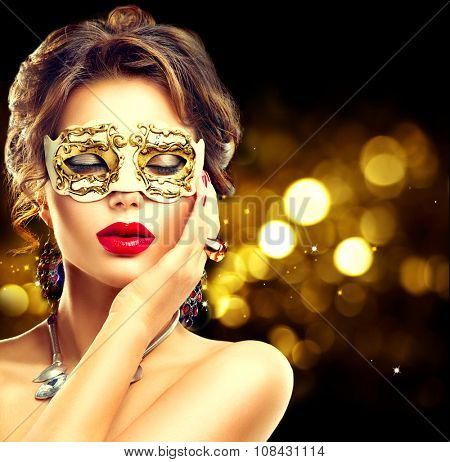 Beauty model woman wearing venetian masquerade carnival mask at party over holiday dark background with magic glow. Christmas and New Year celebration. Glamour lady with perfect make up and hairstyle