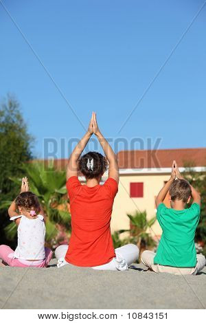 Woman With Children Sit Turn Back On Sand In  Pose Of Yoga And Laying Down Hands Lift Hands Upwards