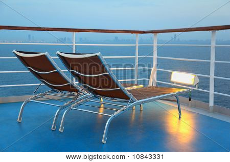 Two Deck-chair Are On The Ship Overlooking The City In The Evening And Illuminated By Yellow Light