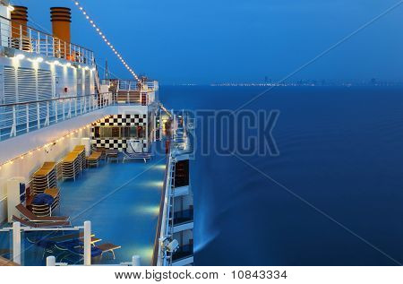 Illuminated Cruise Ship With People In The Sea At Night Near City
