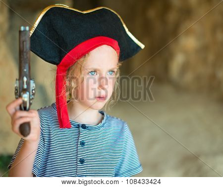 Little Girl In Pirate Costume With Musket Gun Near The Cave Entrance. Place For Your Text.