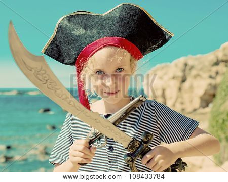 Little Girl In Pirate Costume With Sword And Old Musket Gun.