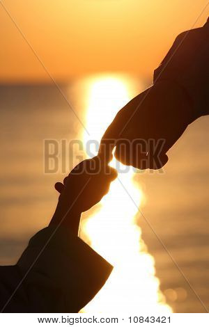 Silhouettes Of Child's And Grown Man Hands Which Adjoin Fingers In Evening Ashore Exterminating
