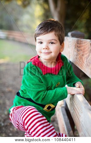 Cute little boy in Christmas clothes standing by a fence
