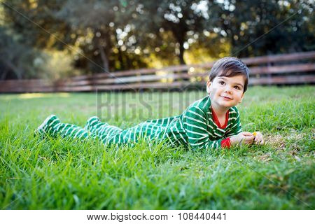 Cute little boy in christmas pajamas outside in the grass