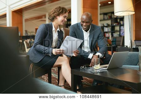Successful Business Partners Going Through Papers In Lobby