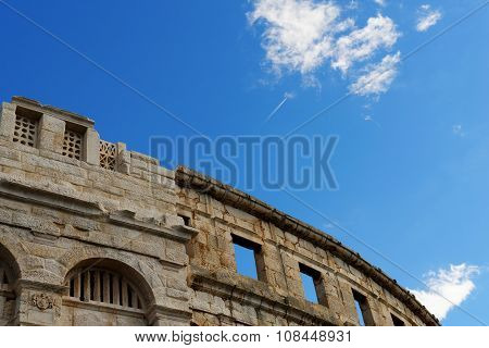 Contrail of the jet plane above ancient Roman amphitheater in Pula Croatia