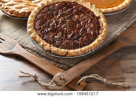Closeup of a fresh baked Pecan pie with wood utensils and burlap table cloth. Two additional pies in the background. Thanksgiving concept.