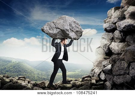 businessman in formal wear holding big stone and walking on the mountains
