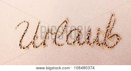 Word  Urlaub written in sand.