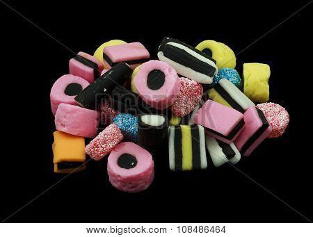 One pile of liquorice allsorts candy isolated on black background