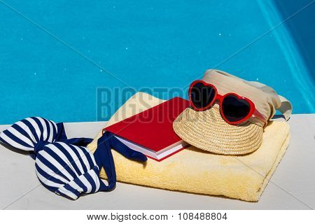 utensils for a nice relaxing vacation day lying next to a swimming pool. recreation on vacation.