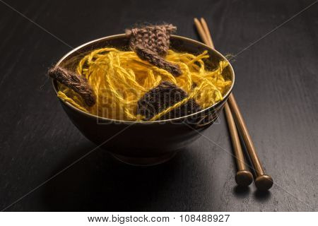 Food Knitted From Woolen Thread Lies On A Plate, As A Japanese Dish Of Meat And Noodles, Lie Next To