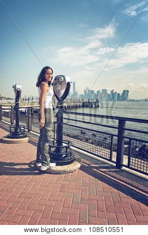 Full Length Portrait of Woman Standing Next to Binocular View Finder with View of New York City Skyline and Liberty Island Pier in Background, New York, USA