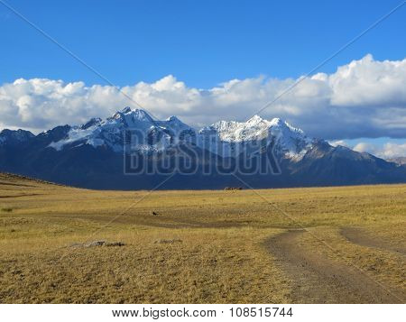 Off the beaten path Empty Rural dirt road in the desert in front of large mountains in the andes in latin america