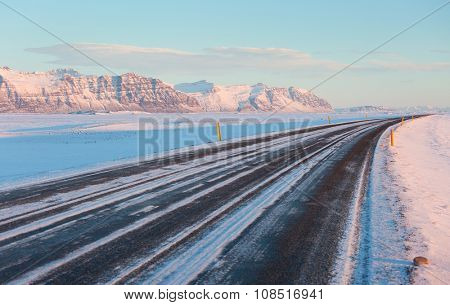 The road on a sunny winter day along  the snow-capped mountains. The Ring Road (Route 1) of Iceland, between Hof and Jokulsarlon. South of Iceland
