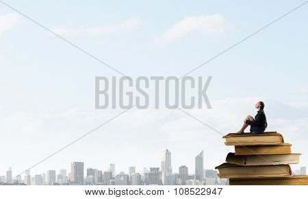 Bored young businesswoman sitting alone on pile of books poster