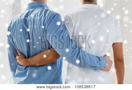 people, homosexuality, same-sex marriage, gay and love concept - close up of happy male gay couple hugging from back over snow effect poster