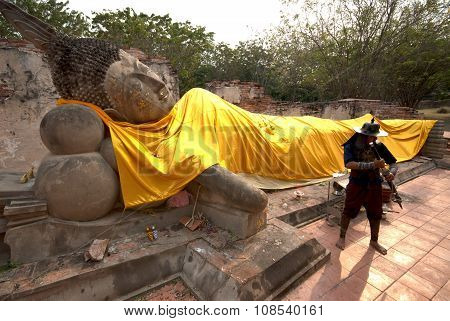 Ancient Warrior Posing Front Of Reclining Buddha.
