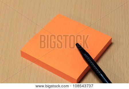 black pen orange paper on wood table background.