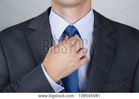Well dressed business man adjusting his neck tie poster