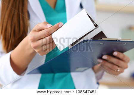 Close-up View Of Female Doctors Hands Holding Patient's Medical Record
