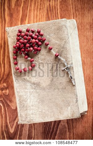 Old book and catholic rosary on wooden background poster