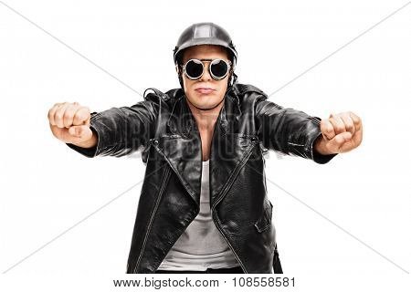 Young biker in a black leather jacket pretending to ride a motorcycle isolated on white background