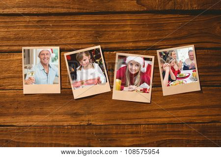 Instant photos on wooden floor against handsome man in santa hat toasting with white wine