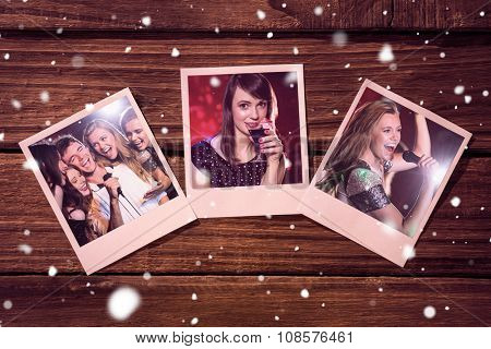 Instant photos on wooden floor against happy friends singing karaoke together