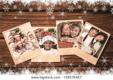 Happy family at christmas against instant photos on wooden floor