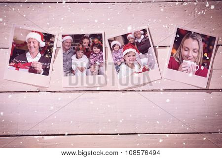 Instant photos on wooden floor against smiling handsome man in santa hat opening a gift