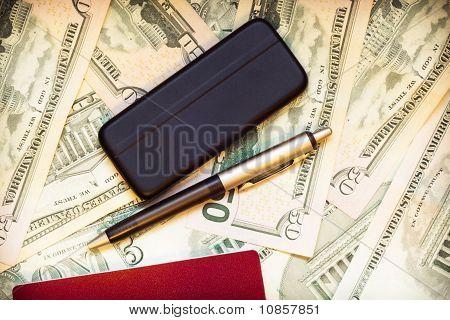 Passport, Phone, Pen And Dollars