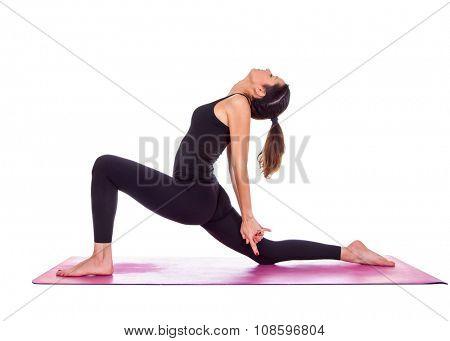 Beautiful woman doing Virabadrasana variant pose on yoga class. Studio shot.