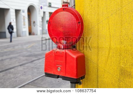 Red Signal Light On Yellow Construction Area Border