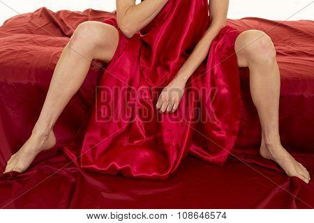 Woman Legs Sitting In Red Sheet