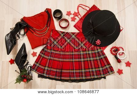 Winter Christmas Sweater And Plaid Skirt With Accessories Arranged On The Floor.